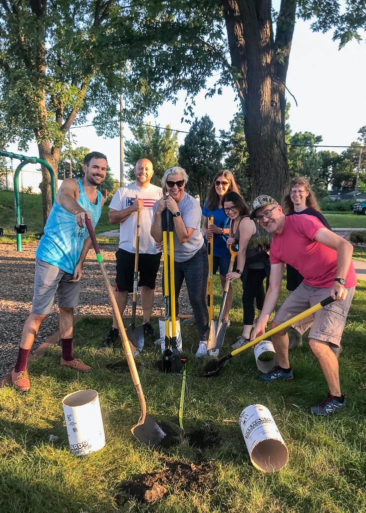 A group of people smile, holding shovels